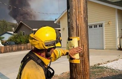 Firefighters post signs in the Spring Valley community near Clearlake Oaks, Calif.