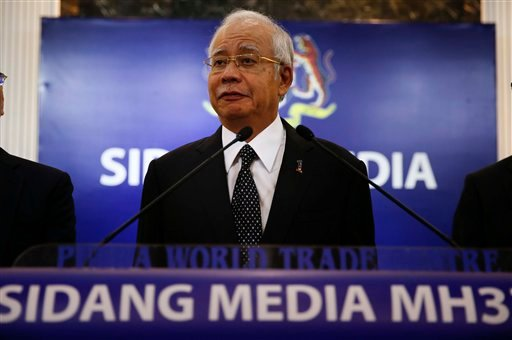 Malaysian Prime Minister Najib Razak, center, speaks at a special press conference announcing the findings for the ill fated flight MH370 in Kuala Lumpur, Malaysia on Thursday, Aug. 6, 2015. (AP Photo/Vincent Thian)