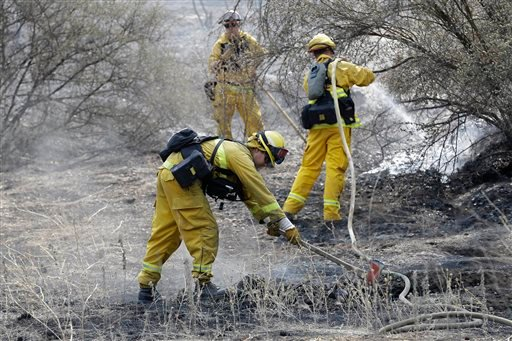 Sonoma Valley Firefighters put out a hot spot from the Rocky Fire near Clearlake, Calif., Wednesday, Aug. 5, 2015. Thousands of firefighters battling an unruly Northern California wildfire were aided overnight by cooler temperatures and higher humidity, b