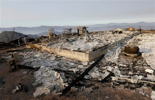 The burned remains of a property is shown near Clearlake, Calif., Wednesday, Aug. 5, 2015. Thousands of firefighters battling an unruly Northern California wildfire were aided overnight by cooler temperatures and higher humidity, but the fire is still les