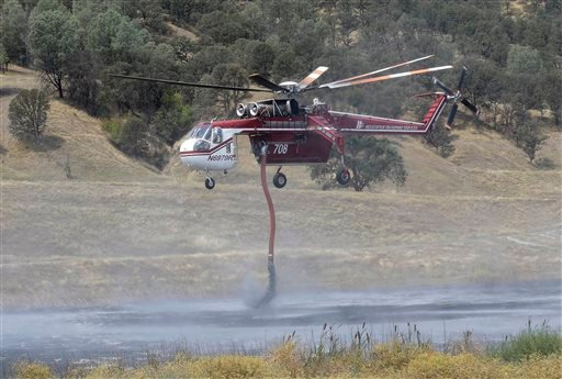 A helicopter pilot takes water from a pond near Clearlake, Calif., Wednesday, Aug. 5, 2015. Thousands of firefighters battling an unruly Northern California wildfire were aided overnight by cooler temperatures and higher humidity, but the fire is still le