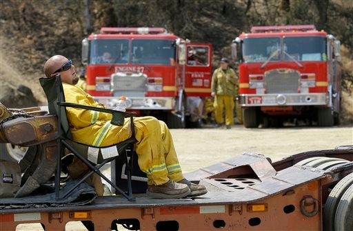 A firefighter rests at a staging area near Clearlake, Calif., Wednesday, Aug. 5, 2015. Thousands of firefighters battling an unruly Northern California wildfire were aided overnight by cooler temperatures and higher humidity, but the fire is still less th