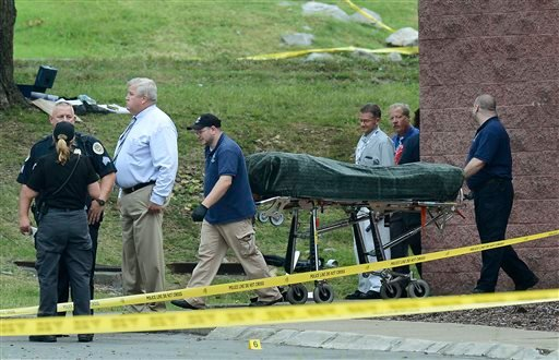 The body of the suspect is removed from a movie theater following a shooting Wednesday, Aug. 5, 2015, in Antioch, Tenn. A man armed with a hatchet and pellet gun unleashed a volley of pepper spray at audience members inside the movie theater, exchanging f