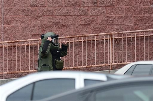 A member of the Nashville Metro Police Bomb Squad walks away from a backpack on the side of a movie theater before detonating it following a shooting Wednesday, Aug. 5, 2015, in Antioch, Tenn. A man armed with a hatchet and pellet gun unleashed a volley o