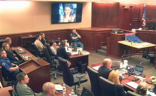 Video image: Family photo of 6-year-old Veronica Moser-Sullivan, one of the people killed in the Colorado movie theater attack, is displayed on the screen above, as shooter James Holmes, second from left Aug. 6, 2015. (Colorado Judicial Department via AP)