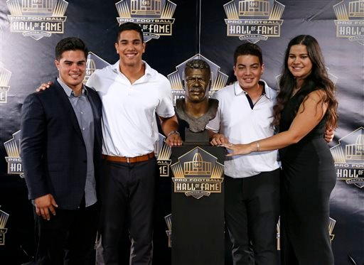 Children of former NFL player Junior Seau, from left, Tyler, Jake, Hunter, and Sydney pose for a selfie with the bust of their late father during inductions at the Pro Football Hall of Fame on Saturday, Aug. 8, 2015, in Canton, Ohio.