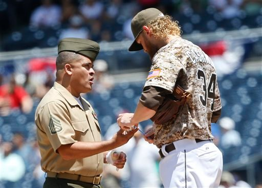 Padres starting pitcher Andrew Cashner signs a ball for a U.S. Marine who took the field with the Padres as part of a Wounded Warrior tribute prior to the baseball game against the Philadelphia Phillies Aug. 9, 2015  in San Diego. (AP Photo/Lenny Ignelzi)
