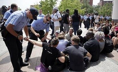 St. Louis police arrest a protester outside the Thomas F. Eagleton Federal Courthouse, Monday, Aug. 10, 2015, AP.