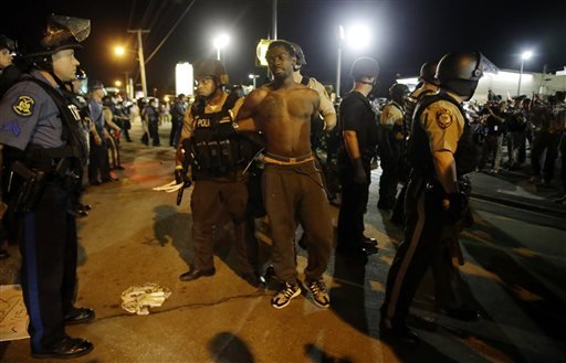 St. Louis County Police make an arrest along West Florissant Avenue Aug. 10, 2015, in Ferguson, Mo. (AP Photo/Jeff Roberson)