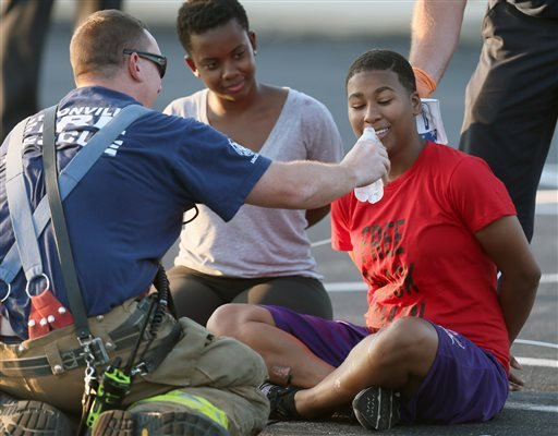 An officer gives water to a detained protester after they blocked rush-hour traffic in both directions on Interstate 70 near the Blanchette Bridge in Earth City, Mo., Monday, Aug. 10, 2015. (David Carson/St. Louis Post-Dispatch via AP)