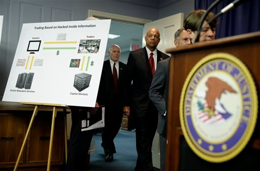 A poster board detailing an insider trading scam involving hacking is displayed at the start of a news conference in Newark, N.J., Tuesday, Aug. 11, 2015.