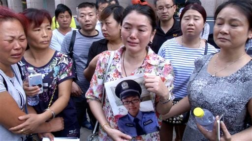 In this image taken from a video footage from AP Video, a woman holds up a photo of her son, a missing firefighter, outside a hotel where officials held a daily media conferences in northeastern China's Tianjin municipality Sunday, Aug. 16, 2015. Angry re