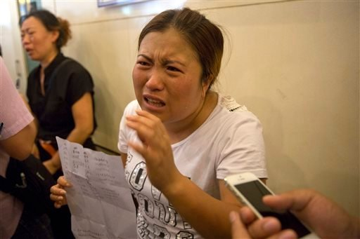 Wang Baoxia talks to a journalist about her missing brother Wang Quan who was at the scene of an explosion in northeastern China's Tianjin municipality, Saturday, Aug. 15, 2015. Angry family members of firefighters missing in the explosions that rocked th