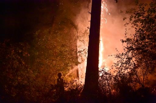 Melanie Brashler(Stevens County Fire District 5)works with in 2-person crew with her husband Larry to fight a flare-up of a wildfire along Townsend-Sackman Road early Aug 15, 2015, in the hills near Addy, Wash.(Tyler Tjomsland/The Spokesman-Review,via AP)