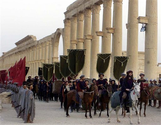 In this Sept. 27, 2002, file photo, a symbolic trade caravan representing the prosperous trade during the era of Queen Zanobya 260-273AD attend a show held in the ancient city of Palmyra, some 240 kilometers (150 miles) northeast of Damascus, Syria. Islam