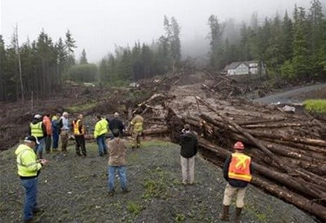 Construction workers and emergency crew members look at the damage caused by a landslide on Kramer Drive, Tuesday, Aug. 18, 2015 in Sitka, Alaska.  AP