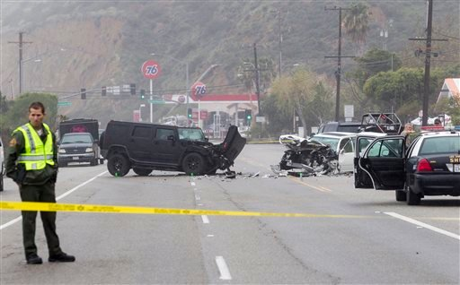 In this Saturday, Feb. 7, 2015 file photo, Los Angeles County Sheriff's deputy guards the scene of a collision involving three vehicles in Malibu, Calif. Sheriff's investigators plan to recommend prosecutors file a vehicular manslaughter charge against Ca