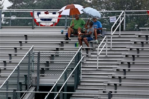 Little League baseball fans sit in the stands at Volunteer Stadium as rain falls Thursday, Aug. 20, 2015, in South Williamsport, Pa.