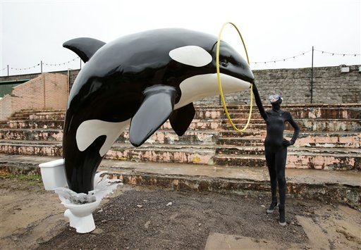 A Banksy piece depicting an orca whale jumping out of a toilet is displayed at Banksy's biggest show to date, entitled 'Dismaland', during a press viewing in Western-super-Mare, Somerset, England.
