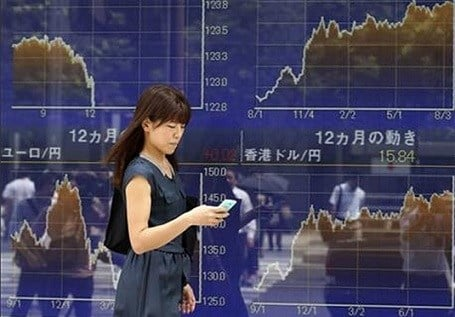 A woman using a smartphone walks by an electronic stock board of a securities firm in Tokyo, Friday, Aug. 21, 2015. Tokyo's Nikkei 225 plunged 2 percent in the morning session as Asian stocks fell further Friday. AP