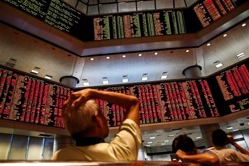 People watch trading boards at a private stock market gallery in Kuala Lumpur, Malaysia on Monday, Aug. 24, 2015. (AP Photo/Joshua Paul)