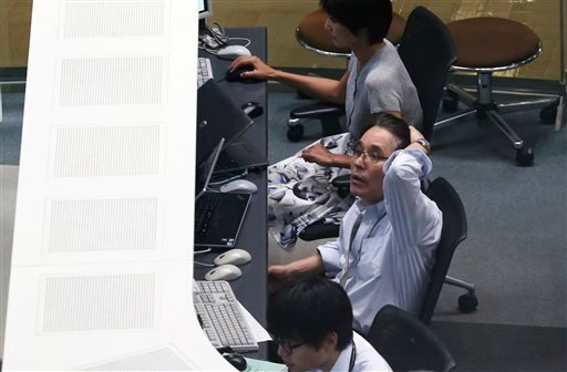 A worker of Tokyo Stock Exchange monitors stock prices on an electric screen during a trading session in Tokyo, Monday, Aug. 24, 2015. (AP Photo/Koji Sasahara)