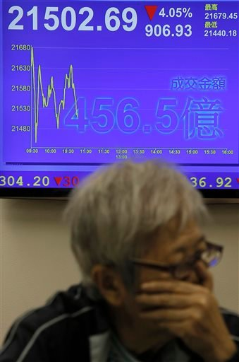 A woman looks at stock index near an electronic board showing the Hong Kong share index at a securities company in Hong Kong, Monday, Aug. 24, 2015. (AP Photo/Vincent Yu)