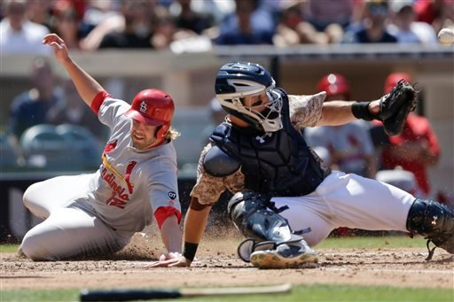 St. Louis Cardinals' Mark Reynolds slides in safely to home, scoring on a sacrifice fly by Matt Carpenter, as Padres catcher Austin Hedges misses the throw during the fourth inning of a baseball game Aug. 23, 2015 in San Diego. (AP Photo/Gregory Bull)