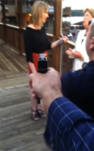 In this framegrab from video posted on Bryce Williams' Twitter account and Facebook page, Williams, whose real name is Vester Lee Flanagan II, aims a gun over the shoulder of WDBJ-TV cameraman Adam Ward at reporter Alison Parker.