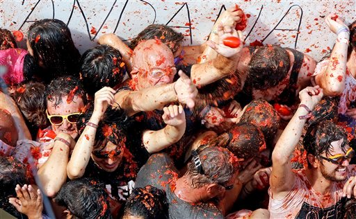 "Crowds of people throw tomatoes at each other during the annual ""tomatina"" tomato fiesta, in the village of Bunol, 50 kilometers outside Valencia, Spain, Wednesday, Aug. 26, 2015. The streets of an eastern Spanish town are awash with red pulp as thousands"
