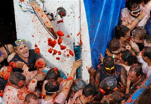 """Crowds of people throw tomatoes at each other, during the annual """"tomatina"""" tomato fiesta, in the village of Bunol, 50 kilometers from Valencia, Spain, Wednesday, Aug. 26, 2015. The streets of an eastern Spanish town are awash with red pulp as thousands o"""
