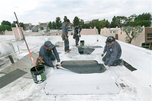 Roofers with Hull Brothers Roofing & Waterproofing resurface townhomes roofs at the Marina del Rey seaside community of Los Angeles on Tuesday, Aug. 25, 2015.