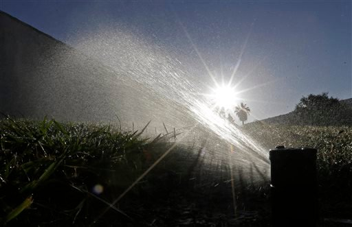In this June 23, 2015, file photo a lawn is irrigated in Sacramento, Calif. A report is due out Thursday, Aug. 27, 2015 on monthly state water conservation figures.