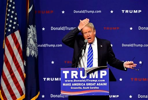 Republican presidential candidate Donald Trump pulls his hair back to show that it is not a toupee while speaking during a rally at the TD Convention Center, Thursday, Aug. 27, 2015, in Greenville, S.C.