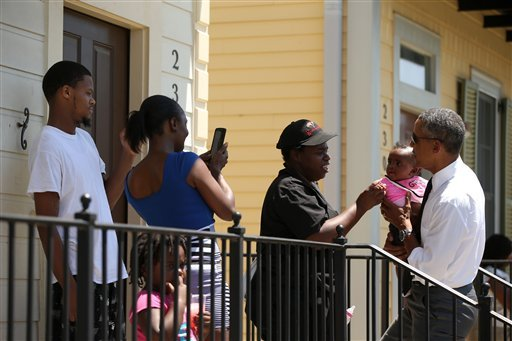 President Barack Obama holds a child as he greets residents in the the Tremé neighborhood in New Orleans, Thursday, Aug. 27, 2015, for the 10th anniversary since the devastation of Hurricane Katrina. Tremé is one of the oldest black neighborhoods in Ameri