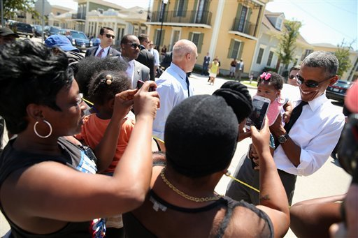 President Barack Obama, accompanied by New Orleans Mayor Mitch Landrieu, holds a child as he greets residents in the the Tremé neighborhood in New Orleans, Thursday, Aug. 27, 2015, for the 10th anniversary since the devastation of Hurricane Katrina. Tremé