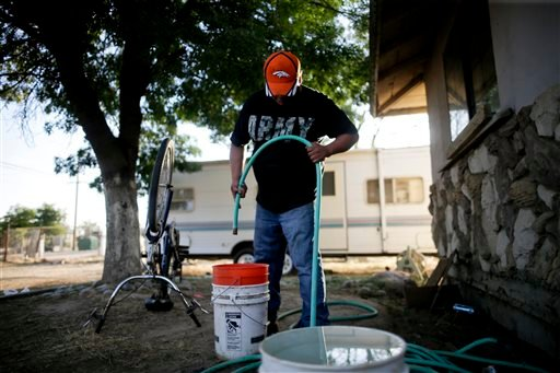"In this June 30, 2015 photo, Tino Lozano looks into a bucket as the last of his available well water drips from a hose in front of his home in the community of Okieville, on the outskirts of Tulare, Calif. ""There it goes. That was all,"" said Lozano, mask"