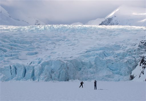 In this March 29, 2006 photo, a skier poses for a photograph on Portage Lake in front of Portage Glacier, about 50 miles south of Anchorage, Alaska. The Portage Glacier, which is a major Alaska tourist destination near Anchorage has retreated so far it no