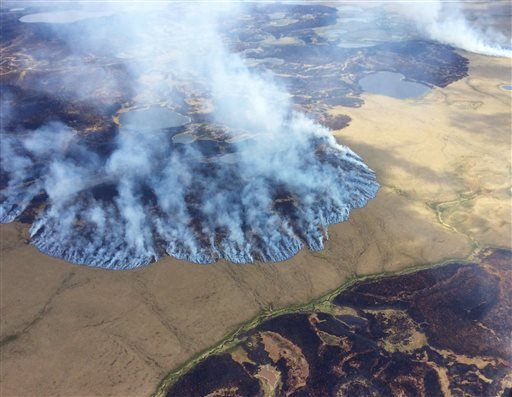 In this Sunday, June 7, 2015 file photo provided by the Alaska Division of Forestry, smoke rises from the Bogus Creek Fire, one of two fires burning in the Yukon Delta National Wildlife Refuge in southwest Alaska. Global warming is carving measurable chan