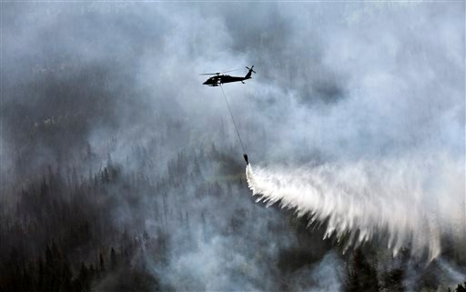 "In this June 17, 2015 file photo provided by the Alaska Army National Guard, a ""Bambi Bucket,"" hanging from a helicopter releases hundreds of gallons of water onto the Stetson Creek Fire near Cooper Landing, Alaska. Global warming is carving measurable ch"