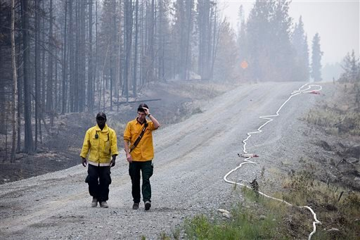 In this June 16, 2015 file photo, two Nikiski Fire Department firefighters walk on a road near a fire-ravaged forest left behind by the Card Street fire in Sterling, Alaska. Global warming is carving measurable changes into Alaska, and President Barack O