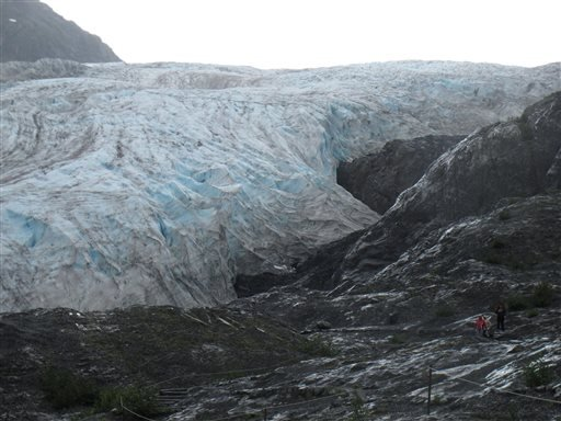 In this Aug. 4, 2012 file photo, tourists walk to Exit Glacier in Kenai Fjords National Park just outside Seward, Alaska. Global warming is carving measurable changes into Alaska, and President Obama is about to see it. Obama leaves Monday, Aug. 31 for a