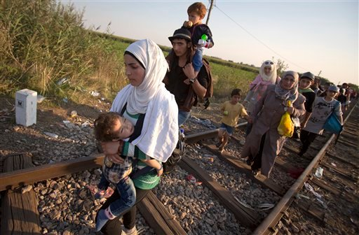 In this Friday, Aug. 28, 2015 photo, refugees walk on the railway tracks to cross from Serbia, near Roszke, southern Hungary. Round the clock, thousands of refugees cross daily along the approximately 110-mile (175-kilometer) border with non-EU member Ser