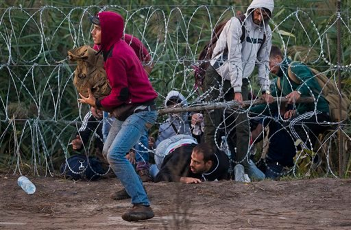 In this Friday, Aug. 28, 2015 photo, refugees cross from Serbia through the barbed wire fence near Roszke, southern Hungary. Round the clock, thousands of refugees cross daily along the approximately 110-mile (175-kilometer) border with non-EU member Serb