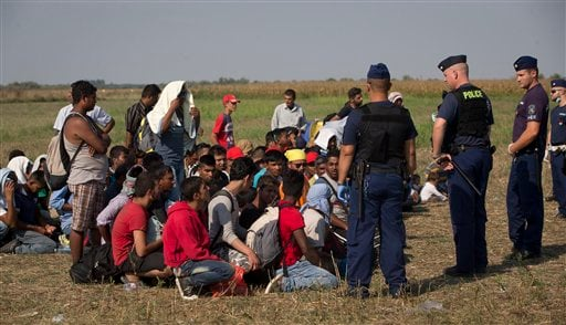 In this Thursday, Aug. 27, 2015 photo, refugees are guarded by Hungarian police after crossing from Serbia, at a detention point near Roszke, southern Hungary. Round the clock, thousands of refugees cross daily along the approximately 110-mile (175-kilome