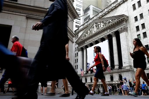 In this Monday, Aug. 24, 2015, photo, pedestrians walk past the New York Stock Exchange. Global stocks mostly fell on Monday, Aug. 31, 2015, after a U.S. (AP Photo/Seth Wenig)