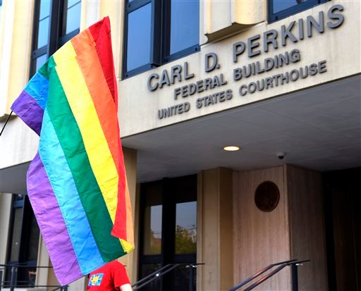 A protester waives a rainbow flag outside the Carl D. Perkins Federal Building in Ashland, Ky., Thursday, Sept. 3, 2015. Rowan County Clerk Kim Davis has defied federal court orders to hand out marriage licenses, saying her religious beliefs don't let her