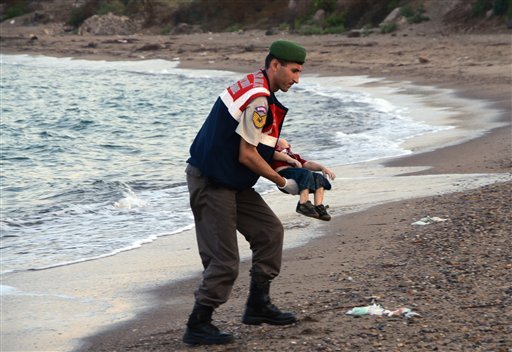A paramilitary police officer carries the lifeless body of Aylan Kurdi, 3, after a number of migrants died and a smaller number were reported missing after boats carrying them to the Greek island of Kos capsized, near the Turkish resort of Bodrum early W