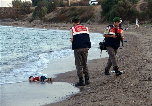 Paramilitary police officers investigate the scene before carrying the lifeless body of Aylan Kurdi, 3, after a number of migrants died and a smaller number were reported missing after boats carrying them to the Greek island of Kos capsized, near the Turk