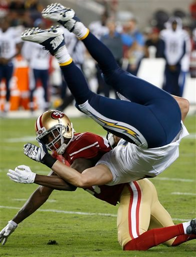 San Diego Chargers tight end John Phillips, top, falls over San Francisco 49ers strong safety Jimmie Ward during the first half of an NFL preseason football game in Santa Clara, Calif., Thursday, Sept. 3, 2015.